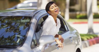 Happy black woman leaning out car window with hands in the air