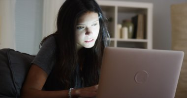 College student staying up late writing her paper on laptop