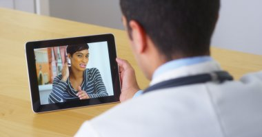 Hispanic doctor talking with young woman patient on tablet