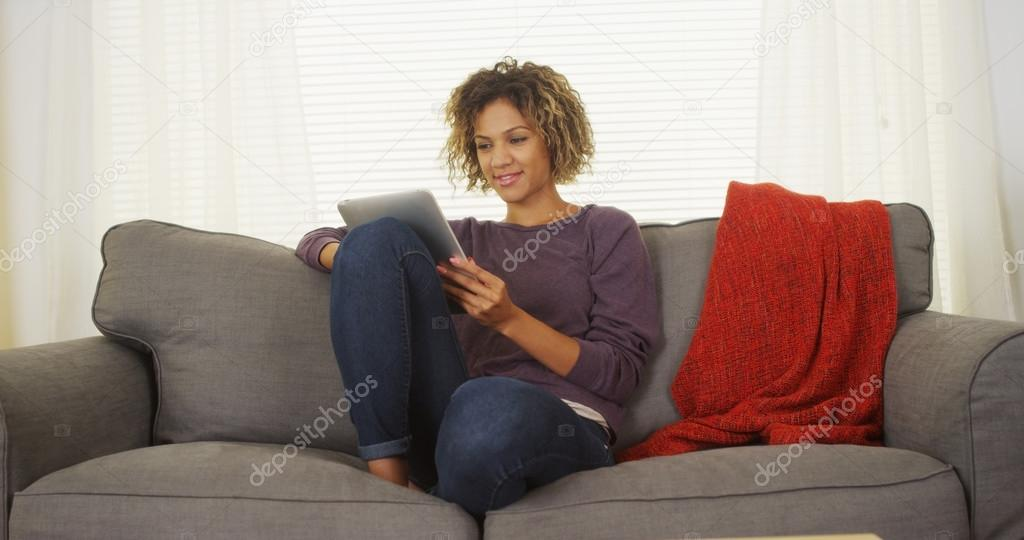 Happy black woman sitting on couch using tablet
