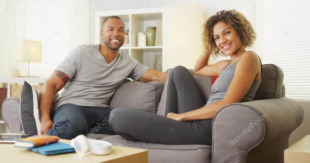 African couple sitting on couch smiling