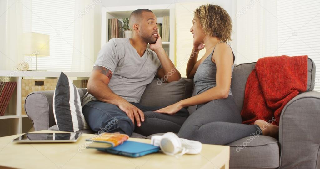 African American couple talking together on couch