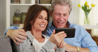 Happy mature couple using smartphone together