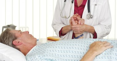 Doctor holding patient's hand and comforting him