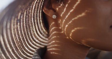 Extreme close up of Black woman with sunhat and diamond earing