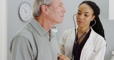 Black doctor listening to senior breathing