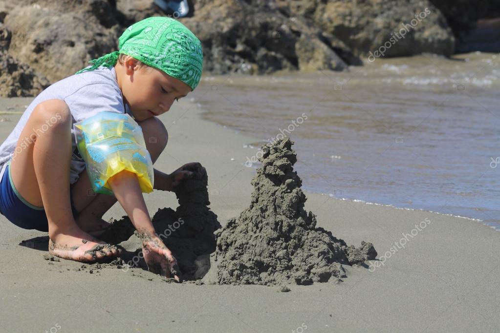 boy builds a sand castle