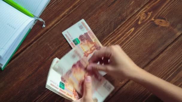 Žena počítá peníze na stůl