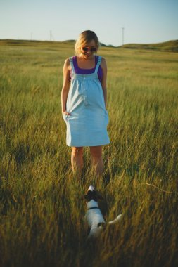 Happy pregnant woman with a dog at sunset