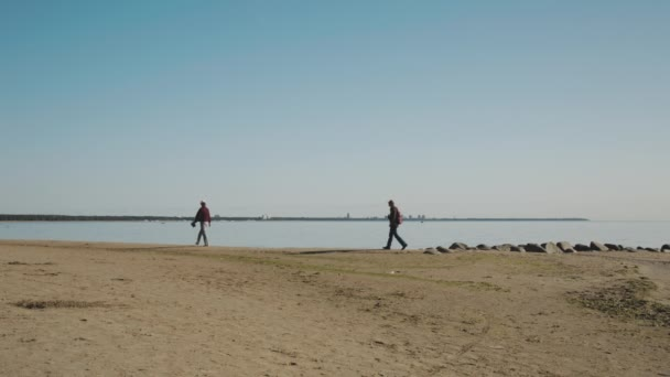 dva lidé chodí na pláži. Petrohrad, Rusko - 11 září 2015
