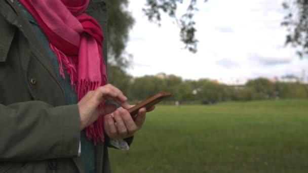 Felnőtt nő használ smartphone a parkban