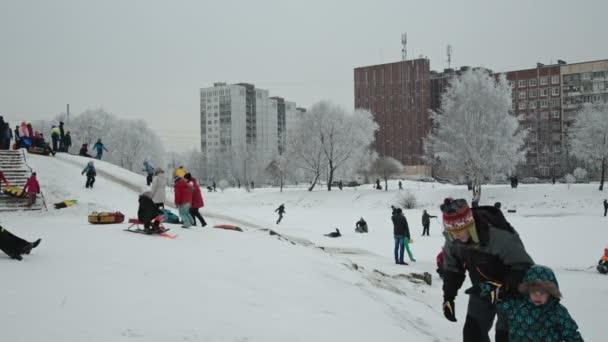 scivoli per bambini giù per una collina di neve nel parco durante il fine settimana