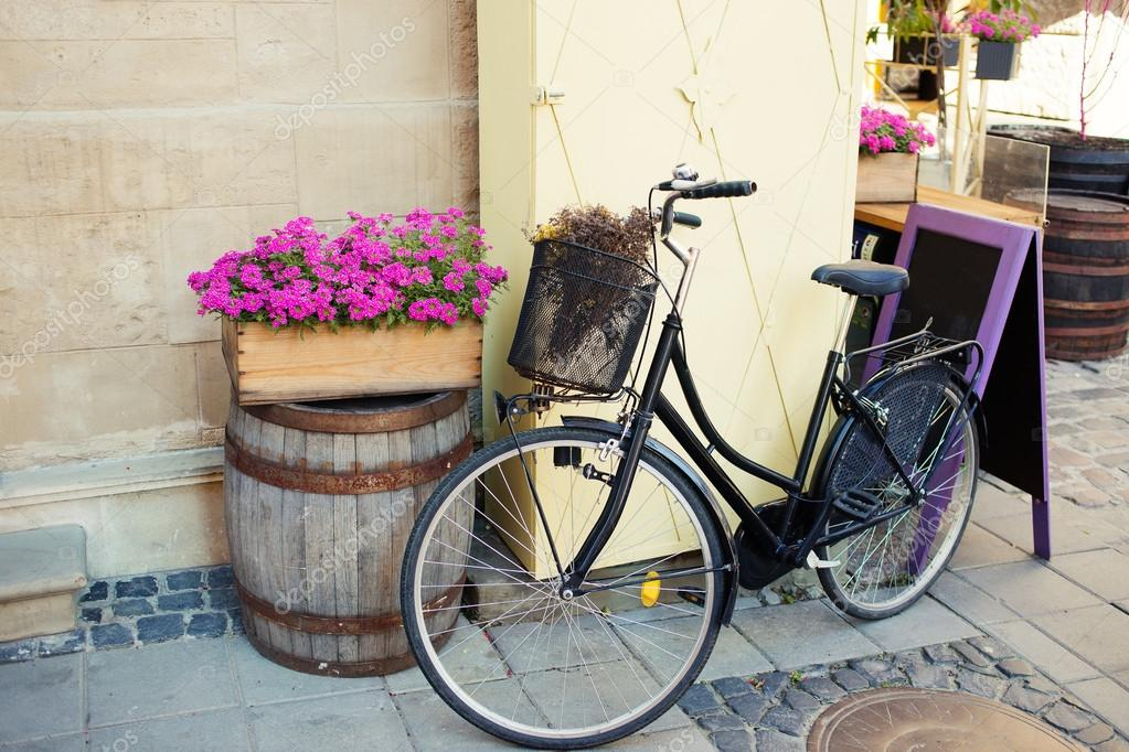 Vintage bicycle with flower basket and chalk board near cafe