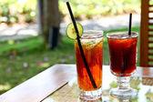 Refreshing lemon iced tea and black tea in the garden