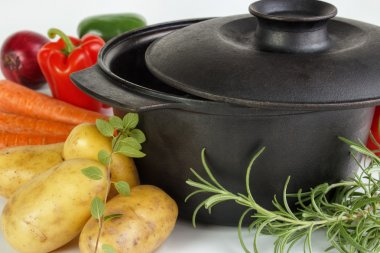 Fresh vegetables and herbs with cast iron pot