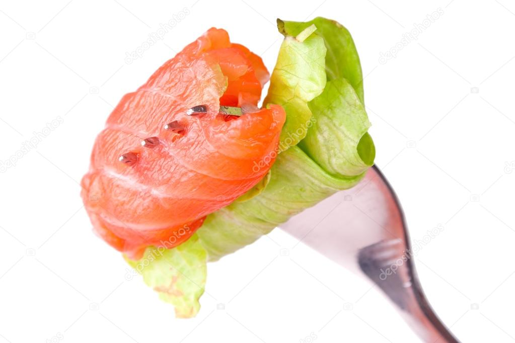 Roll of salmon with leaf of lettuce on a fork