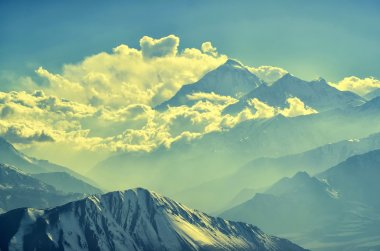 Stunning view to the mysterious silhouettes of snowy mountain peaks and clouds in soft sunset light