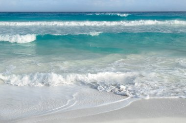 White foamy waves and gradually darkening color of sea water wit
