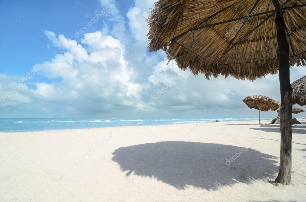 Palm Leaves shadow umbrellas at white sandy beach with turquoise