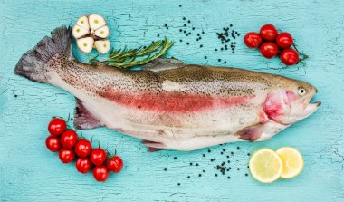 Fresh trout fish with vegetables on blue wooden table.