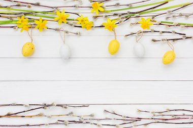 Easter background with decorative Easter eggs, narcissus  and willow tree branch. Copy space