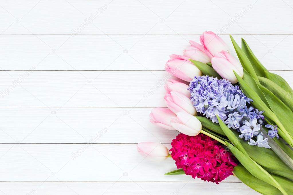 Bouquet of spring flowers on white wooden background. Copy space