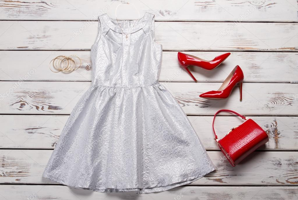 d7d02f9dd9b Silver dress and red shoes. White table with silver dress. Lady s luxury  outfit with accessories. Best merchandise from fashion catalog.