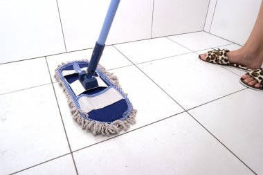 Woman washes the floor in bathroom.