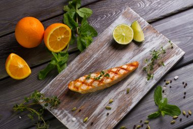 Grilled salmon steak with fresh herbs.