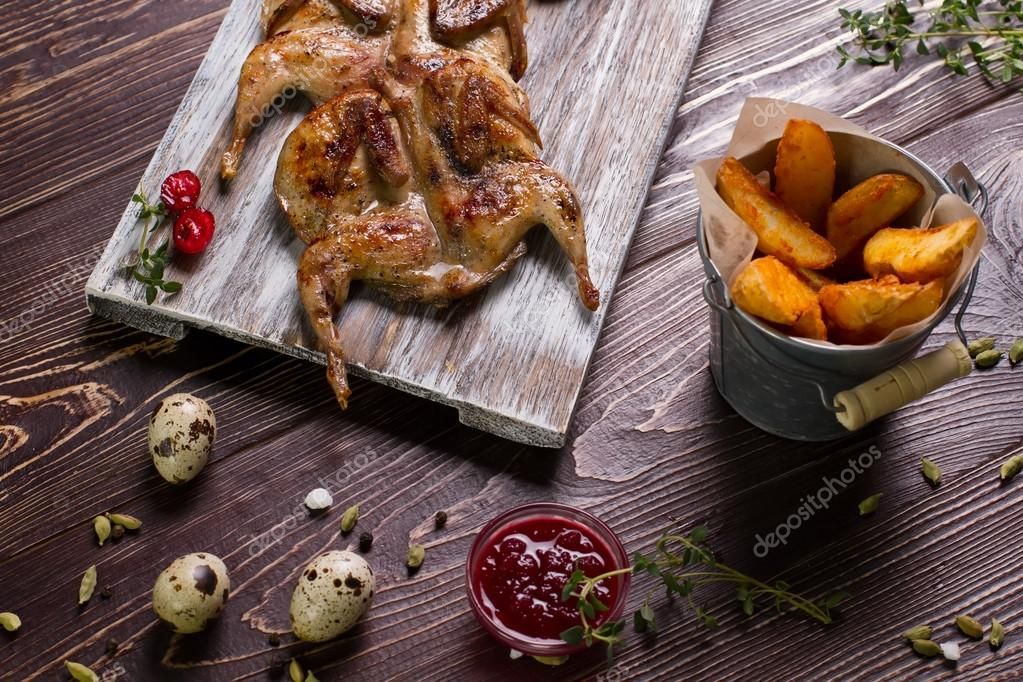 Roasted quails on a wooden board.