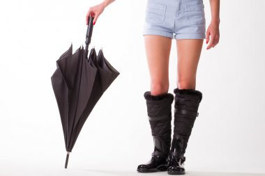 Woman in rubber boots and  black umbrella.