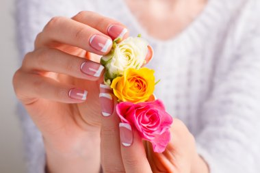 Beautiful gentle french manicure with multicolored roses.