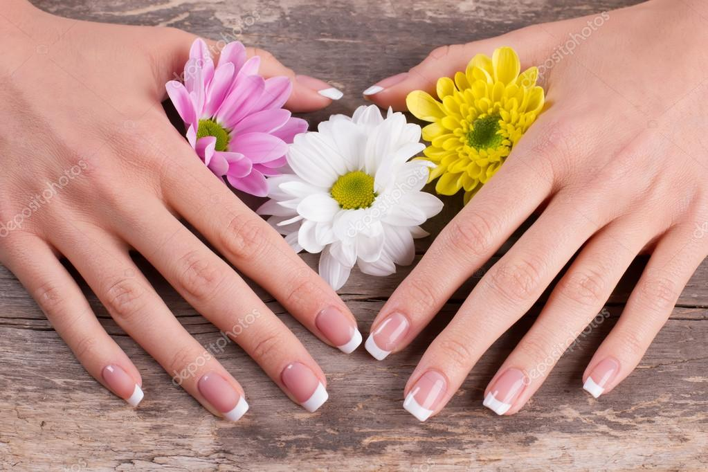 Beautiful french manicure with flowers.