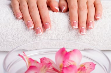 Well-groomed female hands on a towel.