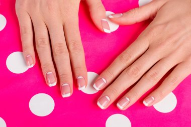 Stylish moon french manicure on a bright pink background.