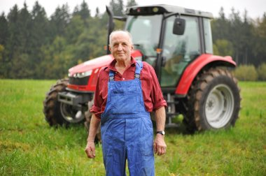 Farmer standing in front of his red tractor
