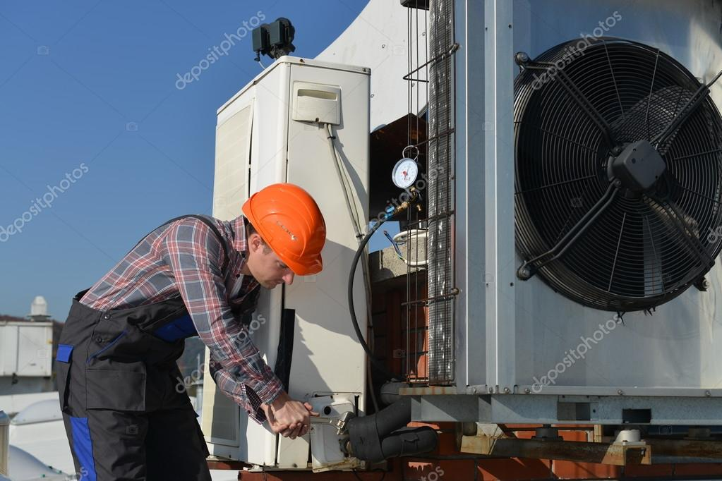 Young repairman on the roof fixing air conditioning system