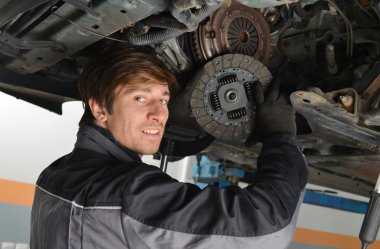 Auto mechanic working under the car