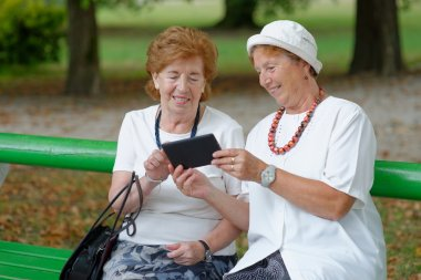 Two senior ladies reading news