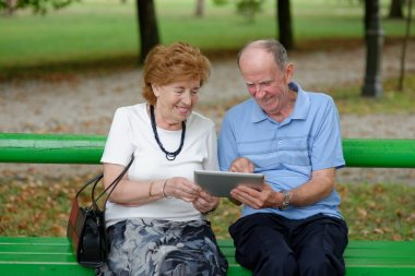 Two senior people sitting with a tablet PC