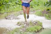 Athletes legs running through puddles. Dirt and water splashes