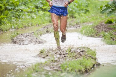 Athlete's legs running through puddles. Dirt and water splashes
