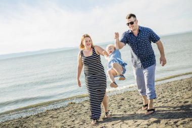 Family of three on beach having fun together