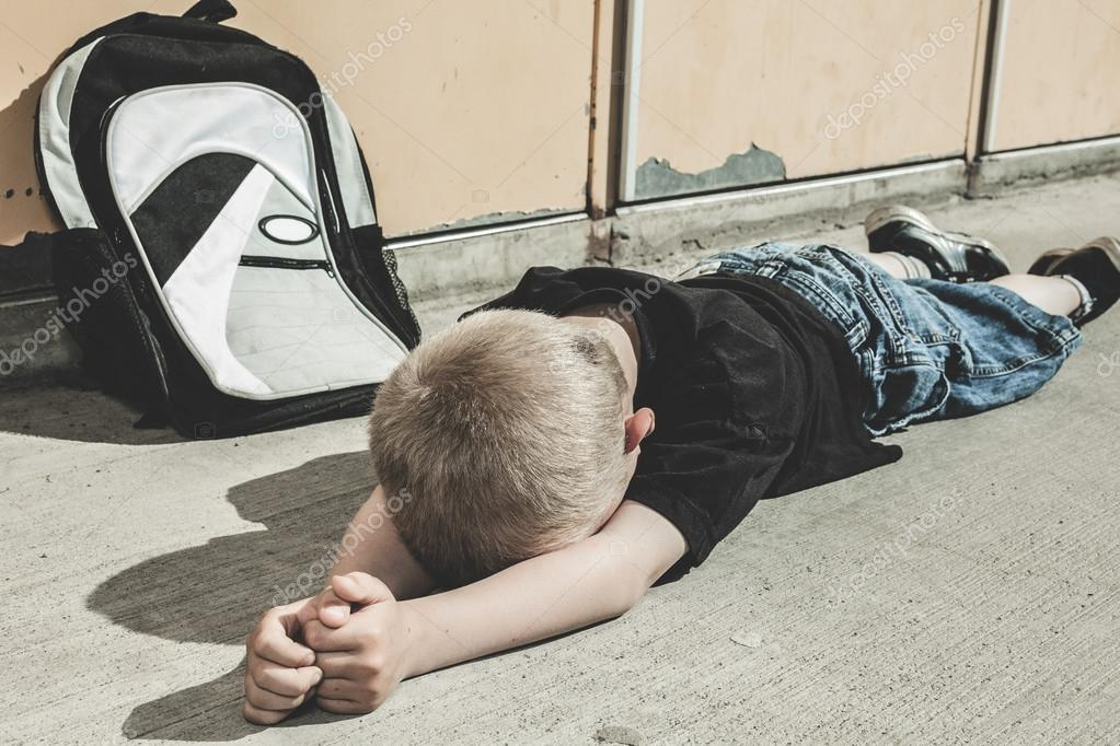 a very sad boy in school playground stock photo lopolo 78159108