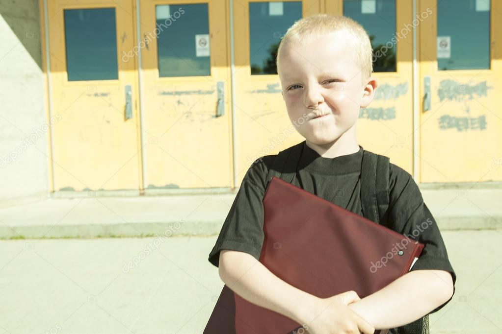 boy on the playground of his school with a backpak