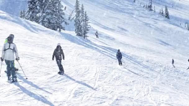 Menschen fahren bei Schneefall Hang hinunter