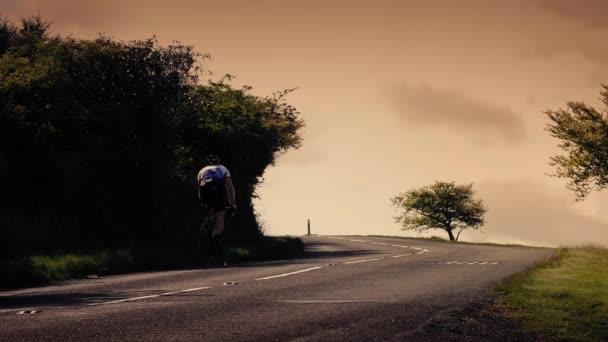 Cyklista jede do kopce při západu slunce s autem kolem