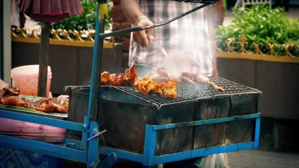 Straßenverkäufer kocht Fleisch auf Räuchergrill