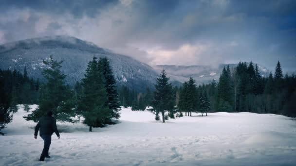 Mann läuft durch tiefen Schnee in gefrorener Landschaft