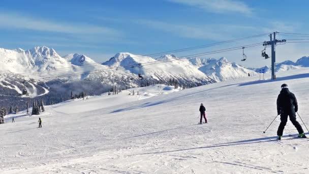 Skiabfahrt mit vielen Skifahrern an sonnigem Tag
